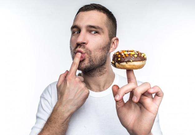 Een man in een wit t-shirt houdt een chocoladedoughnut om zijn vinger
