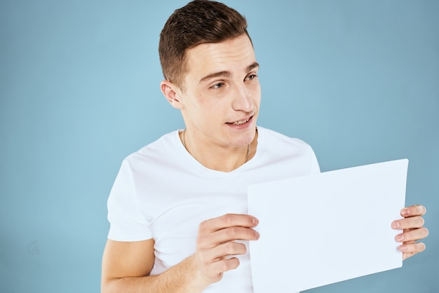Een man in een wit t-shirt houdt een vel papier kopie ruimte vast