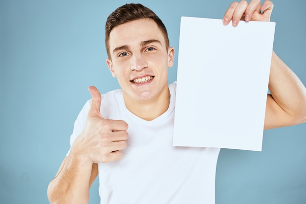 Een man in een wit t-shirt houdt een vel papier met kopie ruimte vast