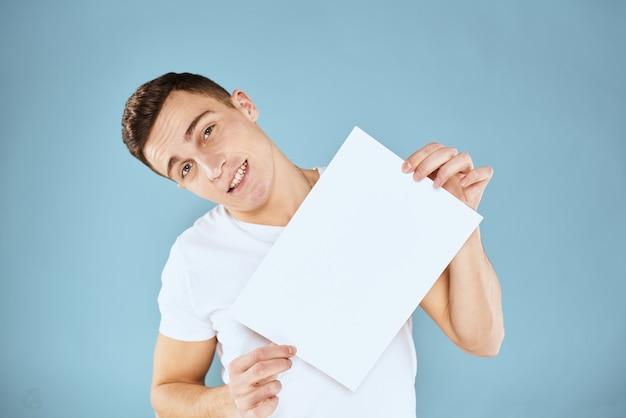 Een man in een wit t-shirt houdt in zijn handen een vel papier emoties bijgesneden weergave van een blauw