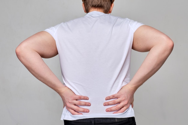 Een man in een wit t-shirt houdt zijn onderrug vast. pijn in de onderrug, wervelkolom, ostejondrose.
