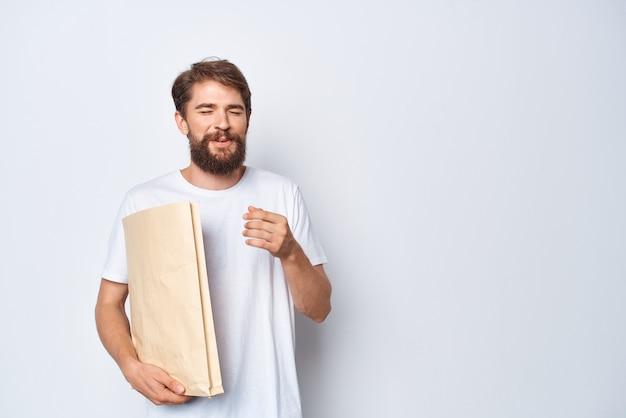 Een man in een wit t-shirt met een papieren zak in zijn handen op een lichte achtergrond