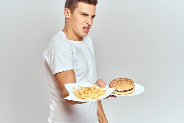 Een man in een wit t-shirt met fast food hamburger in zijn handen