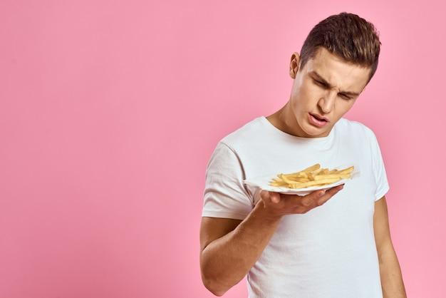 Een man in een wit t-shirt met frietjes in zijn handen
