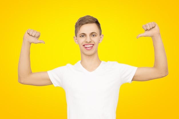 Een man in een wit t-shirt met zijn handen omhoog in de studio op een gele, isolaat