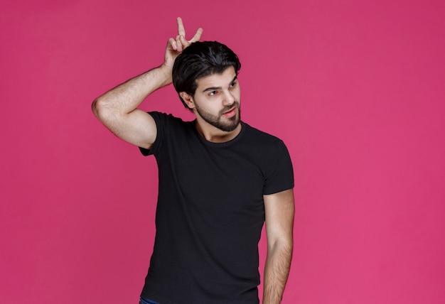 Een man in een zwart overhemd ziet er ontspannen, cool en flirterig uit