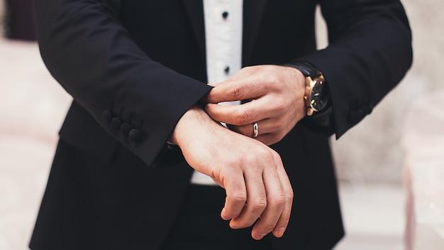 Een man in een zwart pak strekt zijn mouwen