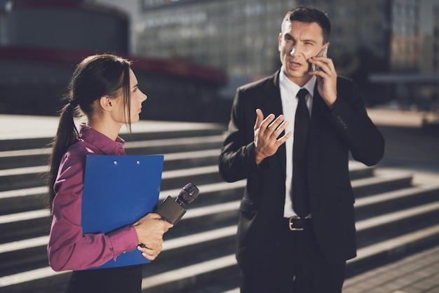Een man in een zwart pak vertelt iets aan de telefoon.