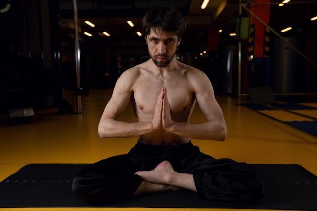 Een man in een zwarte broek en een blote torso zit in sukhasana pose op een zwarte mat in een donkere sportschool. het concept van een gezond lichaam