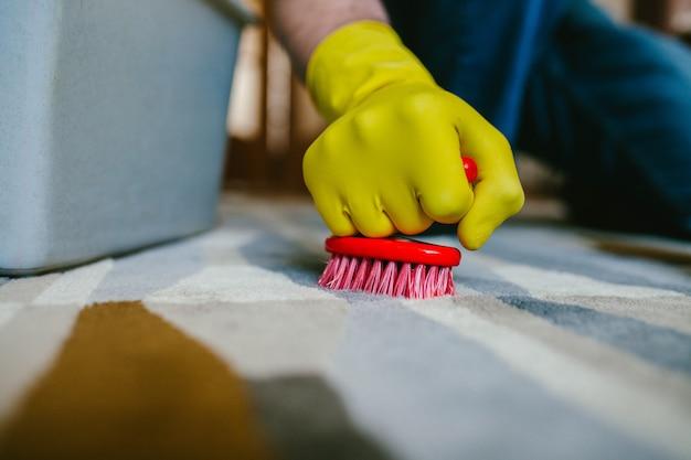 Een man in gele handschoenen wast het tapijt