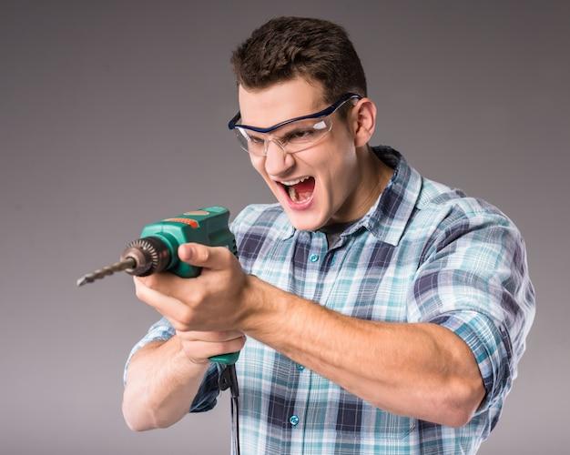 Een man in glazen en houdt een boor in zijn handen.