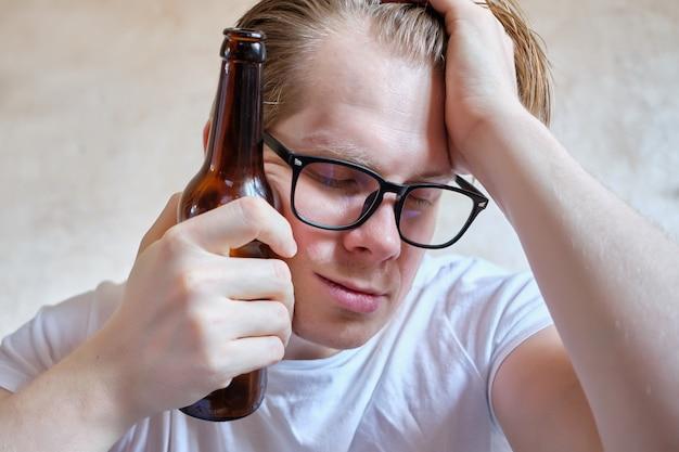 Een man in glazen met een flesje bier rust op zijn hoofd.