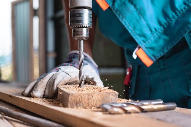 Een man in handschoenen boren van een houten bord close-up. houtbewerking in de werkplaats