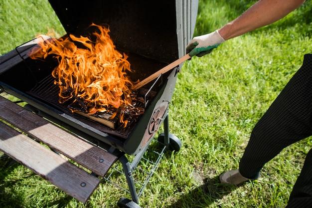 Een man in handschoenen trekt brandend hout in de grill recht. zomer barbecue.