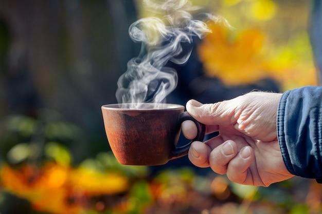 Een man in het herfstbos houdt een kop hete koffie vast, waaruit stoom komt