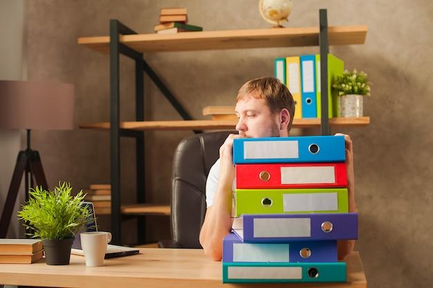 Een man in het kantoor achter een stapel mappen en een laptop.