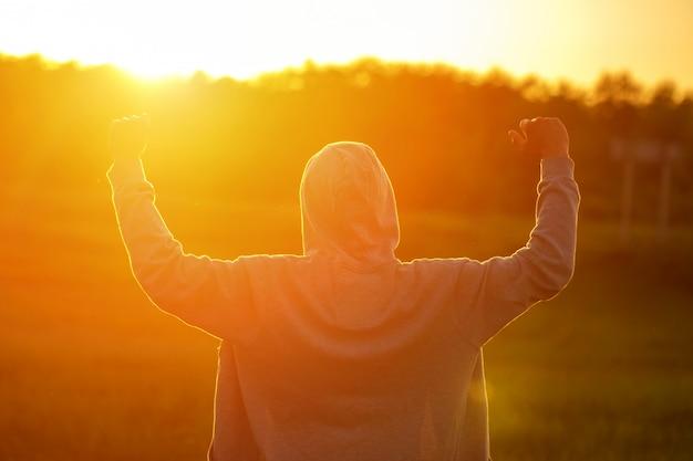 Een man in het licht van de zonsondergang met zijn handen omhoog