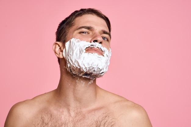 Een man in huiskleren die zijn baard scheert