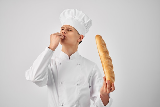Een man in kokskleding met een brood in de handen van een gastronomische werkbakker