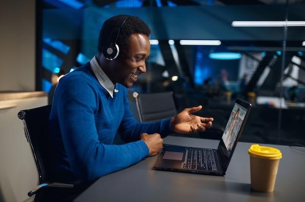 Een man in koptelefoon werkt op laptop in nachtkantoor. mannelijke werknemer, donker zakencentruminterieur, moderne werkplek