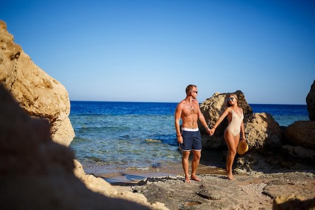 Een man in korte broek en een meisje in een zwempak knuffelen tegen het blauwe water van de rode zee