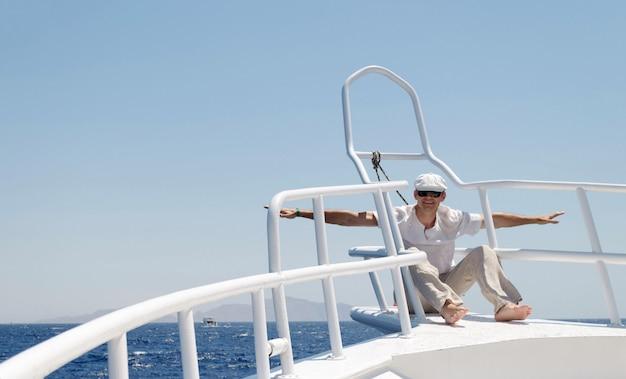 Een man in lichte kleren die een pet en een bril op een jacht draagt, gaat graag weg