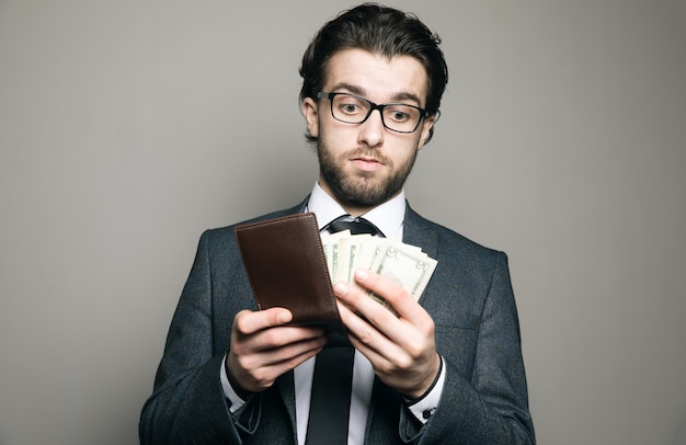 Een man in pak en bril haalt geld uit een portemonnee op een grijze muur