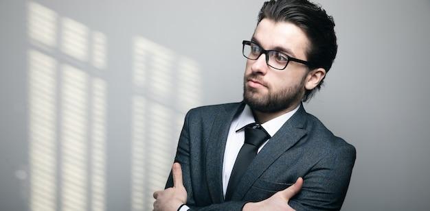 Een man in pak en bril staat met zijn armen gekruist op een grijze muur