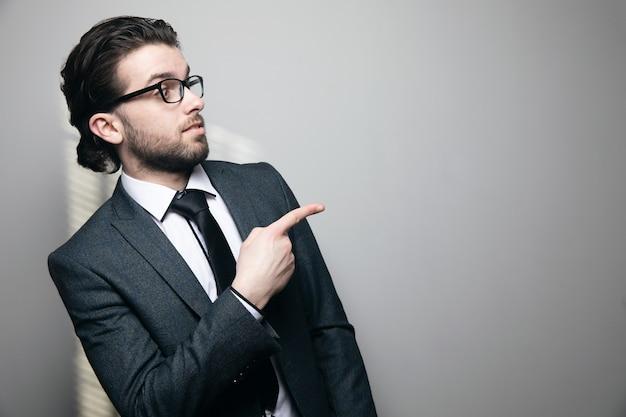 Een man in pak en bril toont een vinger opzij op een grijze muur