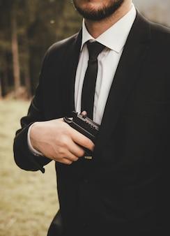 Een man in pak met baard, jasje en wit overhemd, zwarte das, met een pistool in zijn hand op straat.