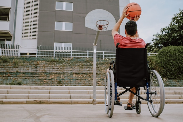 Een man in rolstoel speelt basketbal