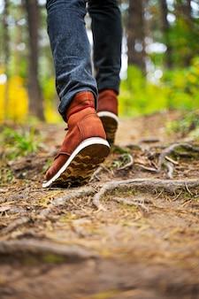 Een man in rood lederen laarzen loopt in het verbazingwekkende herfstbos. schoeisel close-up met kopie spase. reizen concept.