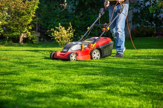 Een man in spijkerbroek maait het gras in de tuin met een grasmaaier zomerdag
