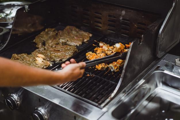 Een man in tatoeages maakt barbecue vlees buiten.