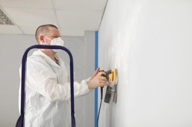 Een man in uniform schuurt pleister op de muur van een huis. reparateur werkt in een kamer met een beschermend masker met gereedschap in zijn handen
