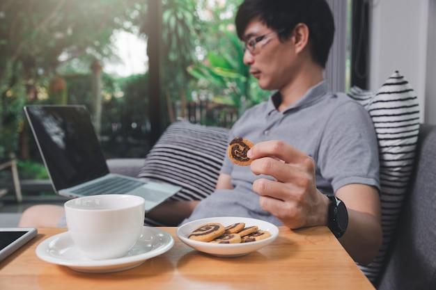 Een man in vrijetijdskleding pakt koekjes terwijl hij op het kantoor aan huis werkt.