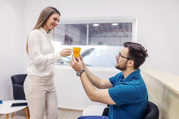 Een man in vrijetijdskleding zit in de wachtkamer voor een technische inspectie en kijkt naar een vrouw die hem een kop warme drank overhandigt