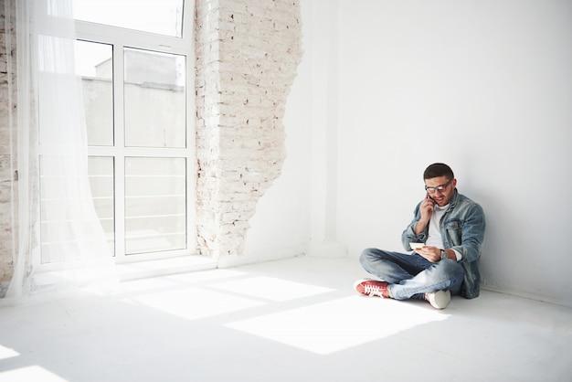 Een man in vrijetijdskleding zit thuis in een leeg appartement en belt aan de telefoon.