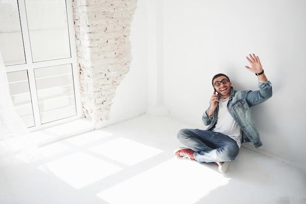 Een man in vrijetijdskleding zit thuis in een leeg appartement met een creditcard en belt aan de telefoon. misschien is hij een nieuwe bewoner en heeft hij nog geen meubels gekocht.