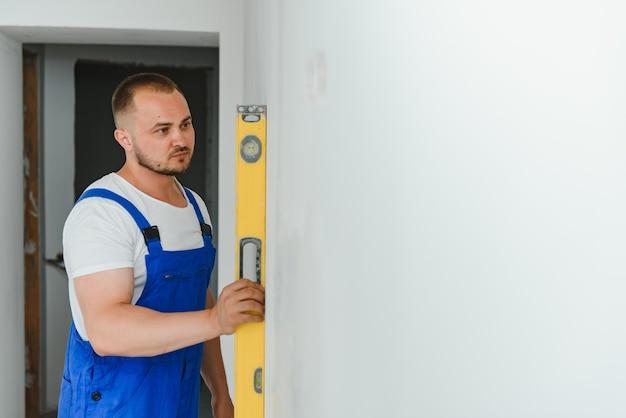 Een man in werkende vorm controleert de vlakheid van de muur met behulp van een gebouwniveau.