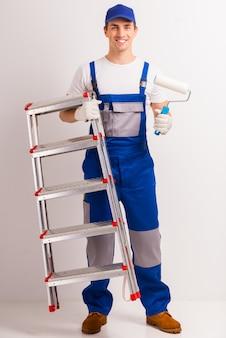 Een man in werkuniform staat met een ladder in zijn handen.