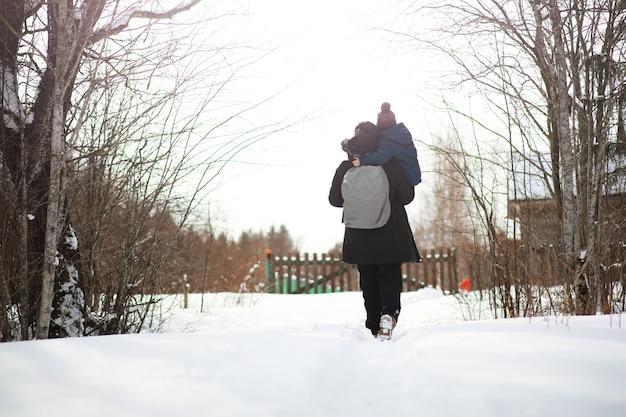 Een man in winterkleren op straat. toeristen reizen door het besneeuwde land. onderweg, wandelen en liften.