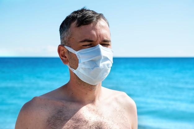 Een man in wit medisch masker aan zee