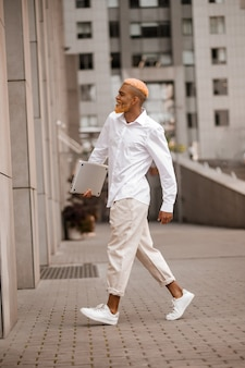 Een man in witte kleren met een gadget in handen