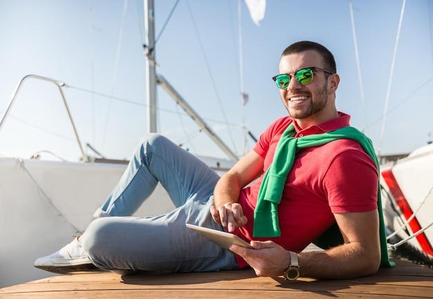 Een man in zonnebril liegt en glimlacht.