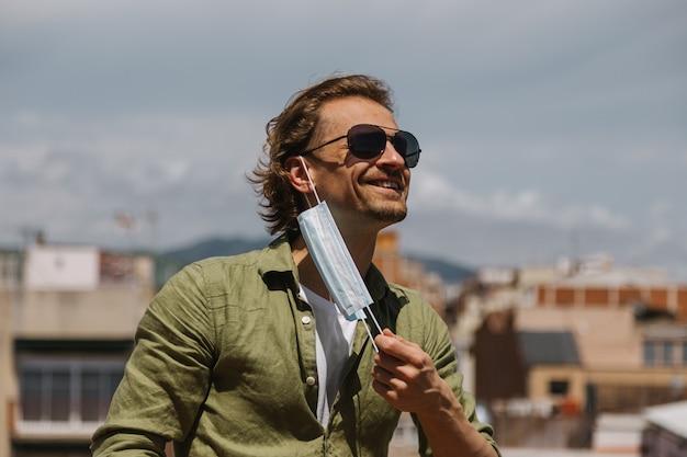 Een man in zonnebril verwijdert met vreugde het medische masker van zijn gezicht op zonnige dag
