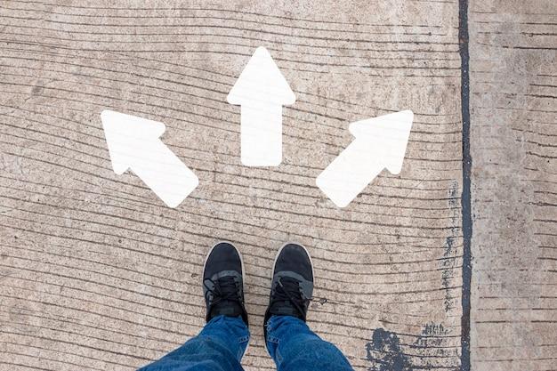 Een man in zwarte gympen staat op een betonnen weg met drie witte richtingspijlen.
