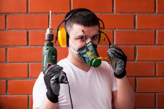 Een man in zwarte handschoenen tegen een rode bakstenen muur in lawaai-verzwakkende hoofdtelefoons.