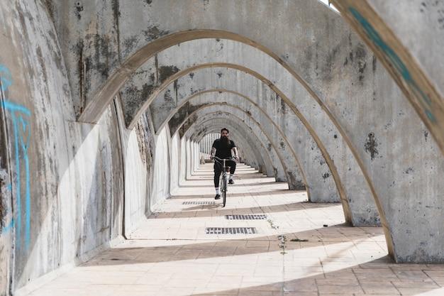 Een man in zwarte kleding die de fiets in overwelfde galerij berijdt