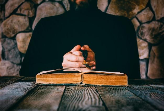 Een man in zwarte kleding met een gebed parelt in de hand biddend voor een oud open boek.